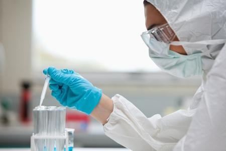 laboratorio: Cerca de un l�quido cient�fico protegidos mujer cayendo en un tubo de ensayo en un laboratorio