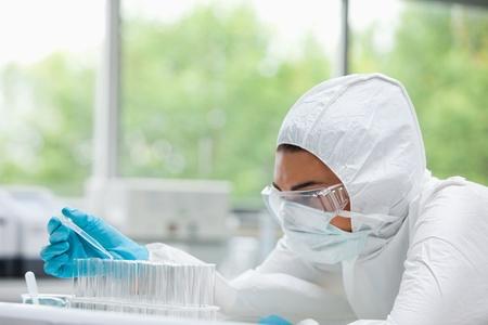 industria quimica: Científico protegidos mujer cayendo líquido en un tubo de ensayo en un laboratorio Foto de archivo