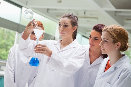 Cute science students pouring liquid in a flask in a laboratory photo