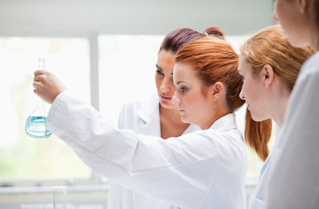 Cute chemistry students holding a flask in a laboratory Stock Photo - 11189878