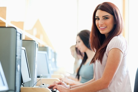 studious: Smiling student using a computer in an IT room Stock Photo