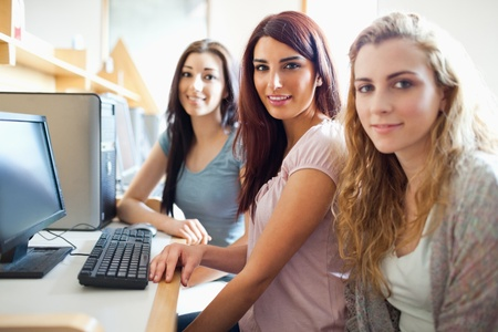 Cute fellow students posing with a computer with the camera focus on thr background model Stock Photo - 11186482