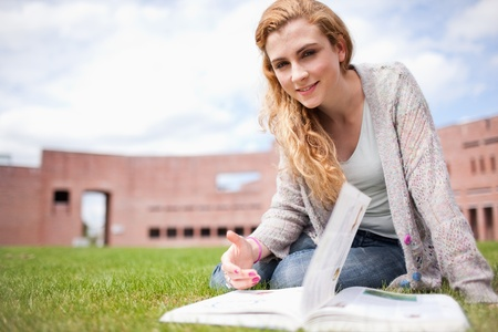 Woman posing with a book while sitting on the lawn photo
