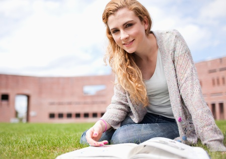 Young woman posing with a book while sitting on the lawn photo