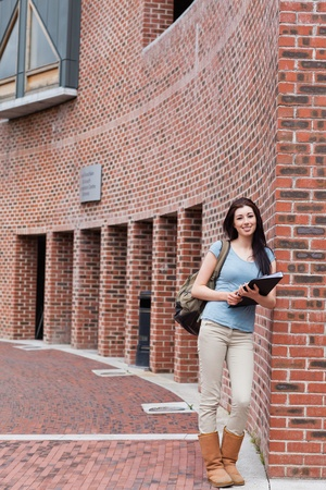 Portrait of a smiling woman with a binder standing outside a building photo