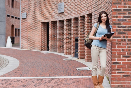 Smiling woman with a binder standing outside a building photo