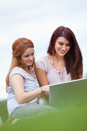 Portrait of women using a notebook while sitting on the lawn Stock Photo - 11188223