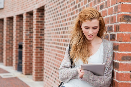 Young student using a tablet computer outside a building Stock Photo - 11185453