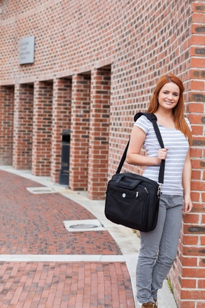 Portrait of a smiling student standing up outside a building photo