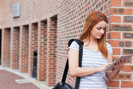 college building: Serious student using a tablet computer outside a building
