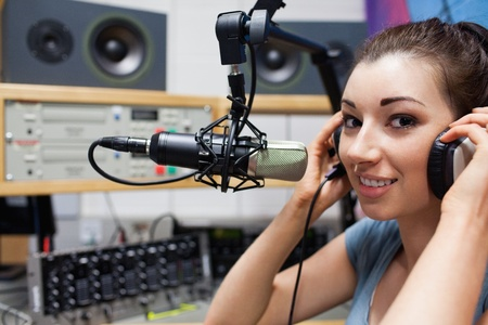 work station: Young radio host putting her headphones on in a station