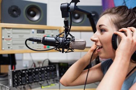 live entertainment: Giovane conduttore radiofonico che parla attraverso un microfono