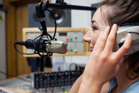 Smiling radio host speaking through a microphone photo