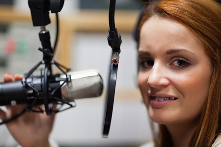 Radio host posing with a microphone photo