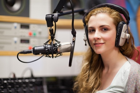 radio station: Young woman posing with a microphone in a studio Stock Photo