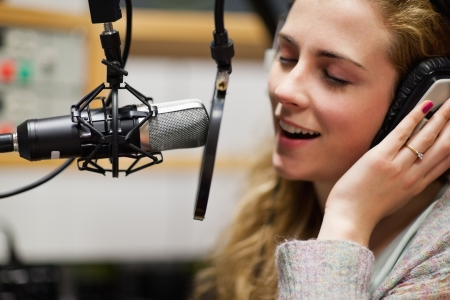 Close up of a singer recording a track in a studio photo