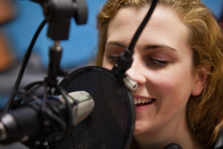 Close up of a young singer recording a track in a studio photo