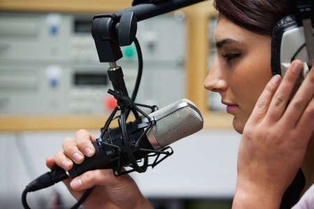 Close up of a cute singer recording a track in a studio photo