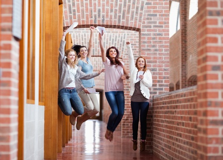 test result: Students jumping with their results in a corridor