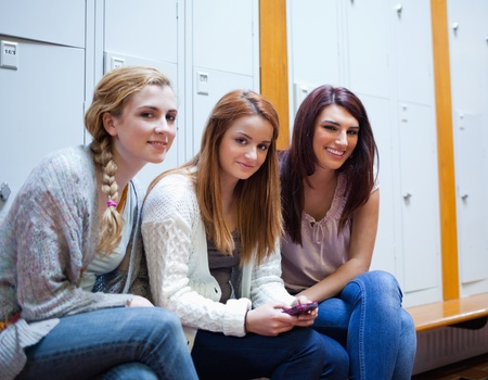 Friends posing with a cellphone in a cloakroom photo