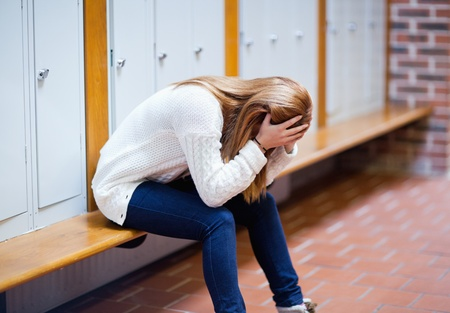 dismiss: Depressed student sitting on a bench in a corridor