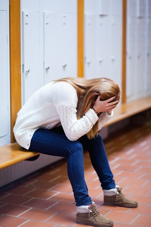 disregard: Portrait of a depressed student sitting on a bench in a corridor Stock Photo