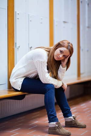 Portrait of a sad student sitting on a bench looking at the camera photo
