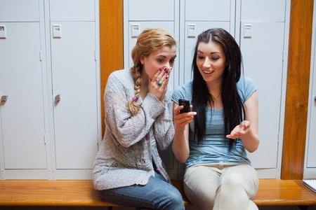 message sending: Surprised student showing a text message to her friend while sitting on a bench Stock Photo