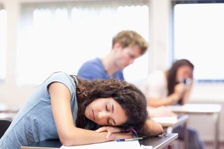 Estudiante durmiendo en su escritorio en un salón de clases Foto de archivo