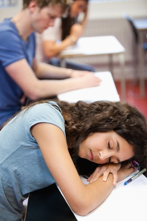 Portrait of a student sleeping on her desk in a classroom photo