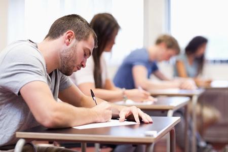 handsome student: Estudiante guapo escribiendo un trabajo en un sal�n de clases