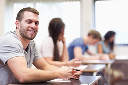 paying attention: Smiling young man sitting in a classroom