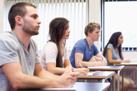 four classes: Studious young adults listening a lecturer in a classroom