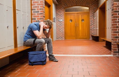 Sad student sitting on a bench in a corridor photo