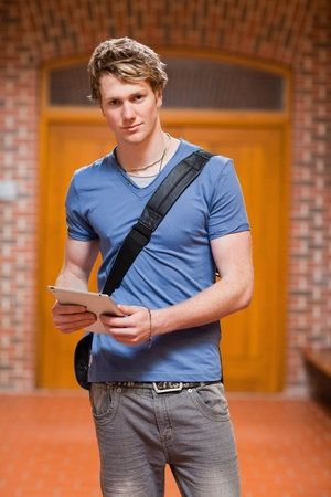 Portrait of a handsome student with a tablet computer in a corridor photo