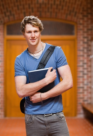 Portrait of a handsome student holding a book in a corridor photo