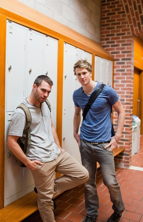 Portrait of handsome students standing up in a corridor photo