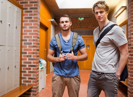 Handsome students posing in a corridor photo