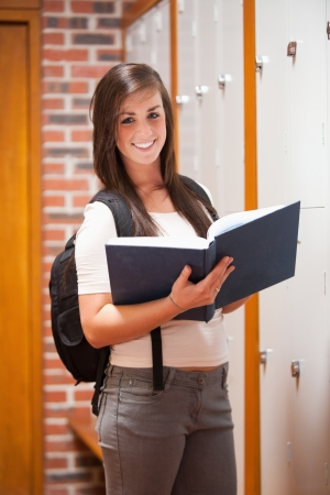 Portrait of a student holding a book in a corridor photo