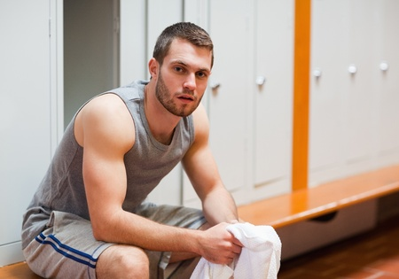 Young sports student sitting on a bench in a corridor photo