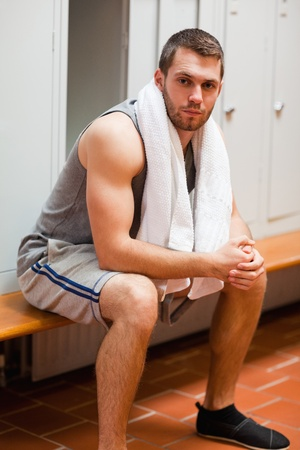 Portrait of a sports student sitting on a bench with a towel photo