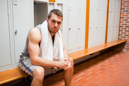 Handsome young sports student sitting on a bench with a towel photo