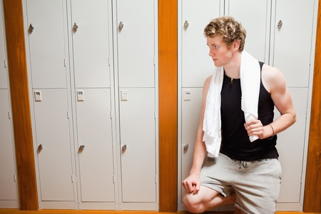 Handsome young sports student leaning on a locker with a towel photo