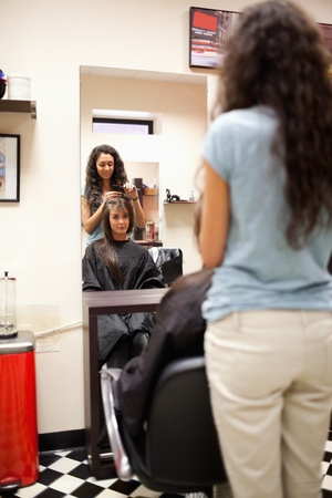 Portrait of a woman combing the hair of a customer standing up photo