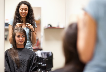 Woman combing the hair of a customer standing up photo