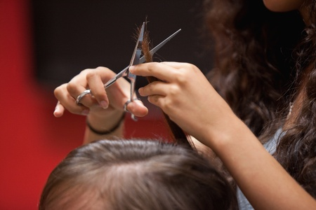 Close up of a hand cutting hair with a scissor  photo