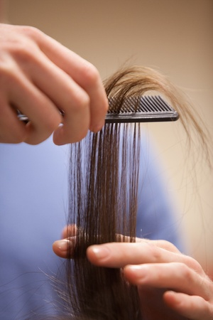 Close up of a hand combing hair with a comb photo