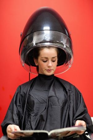 Portrait of a woman under a hairdressing machine against a red background photo