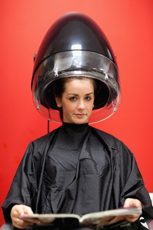 Portrait of a young woman under a hairdressing machine while looking at the camera photo