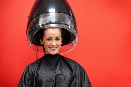 Woman under a hairdressing machine against a red background photo